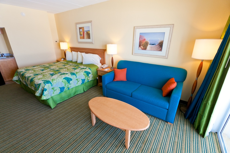 Blue love seat and bed with ocean nearby
