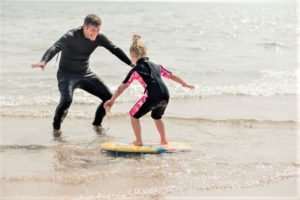 Child receiving an Outer Banks surfing lesson