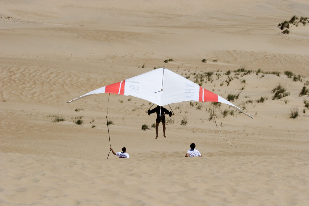 A photo of someone hang gliding on Kill Devil Hills sand dunes