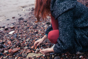 A photo of someone looking for sea glass along Outer Banks shores in winter.