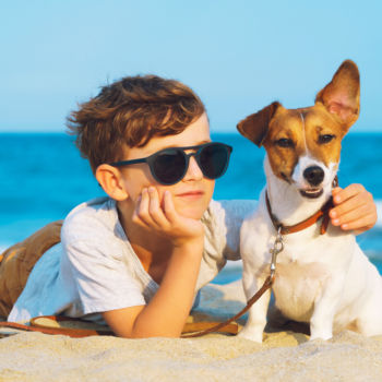 Photo of a Child with His Pup During a Outer Banks Dog-Friendly Vacay